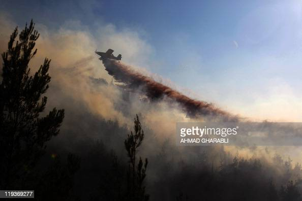 A firefighting plane sprays retardant chemical over flames as it tries extinguish a large forest fire that raged out of control in Jerusalem on July...