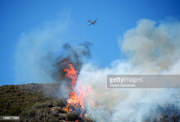 A firefighting plane surveys the Powerhouse wildfire as it continues to burn near Lake Hughes on June 3 2013 in Palmdale California Nearly 2200...