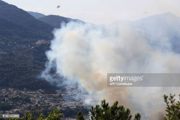 Firefighting planes fly over houses as they try to extinguish a fire in Castagniers near Nice on July 17 2017 / AFP PHOTO / Valery HACHE