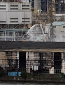 A firefighting snorkel lays down water over a smouldering steel plant beside a river in Kawasaki near Tokyo's Haneda airport on August 24 2015 A huge...