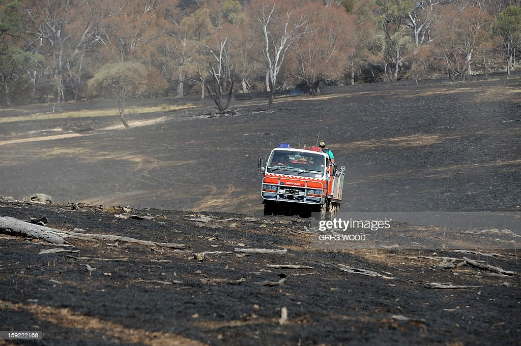 A firefighting vehicle crosses paddocks blackened by a recent bushfire near Bookham, a small village in the Yass Shire in the southern region of Australia's New South Wales state, on January 10, 2013. Fires have been raging across Australia for nearly a week and while many have been contained, 126 are still burning and at least 15 remain out of control in the country's most populous state, New South Wales. AFP PHOTO / Greg WOOD