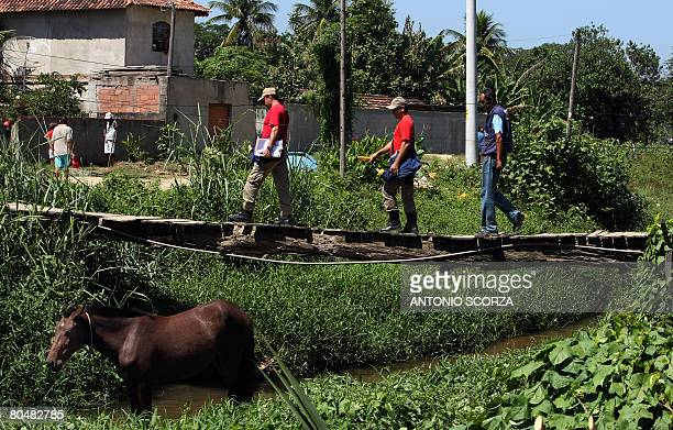 Firefigthers cross a bridge while looking for possible focus of Aedes aegypt mosquitos on April 2 in Vargem Grande 80 kilometres west from downtown...