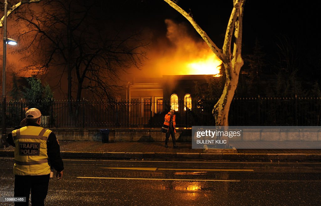 A fireman (R) and a policeman stand as Istanbul fireteams try to control flames during a fire at Galatasaray University on January 22, 2013, in Istanbul.