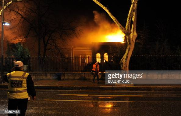 A fireman and a policeman stand as Istanbul fireteams try to control flames during a fire at Galatasaray University on January 22 in Istanbul AFP...