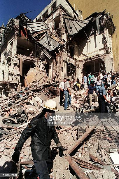A fireman and rescue workers search the remains of the Israeli embassy 17 March 1992 after a powerful bomb exploded causing heavy damage and injuring...