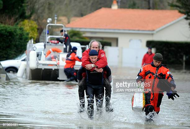 A fireman carries a man on a flooded street in L'AiguillonsurMer western France on March 1 following hurricaneforce winds surging seas and driving...