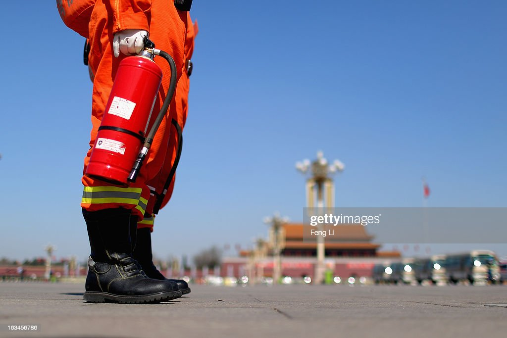 A fireman carrying a fire extinguisher stands on the Tiananmen Square during a plenary session of the National People's Congress on March 10, 2013 in Beijing, China. The State Council, China's cabinet, will begin its seventh restructuring attempt in the past three decades to roll back red tape and reduce administrative intervention. Several departments under the State Council will be reorganized according to a plan on the institutional restructuring and functional transformation of the State Council, which was submitted to the plenary session of the National People's Congress Sunday.