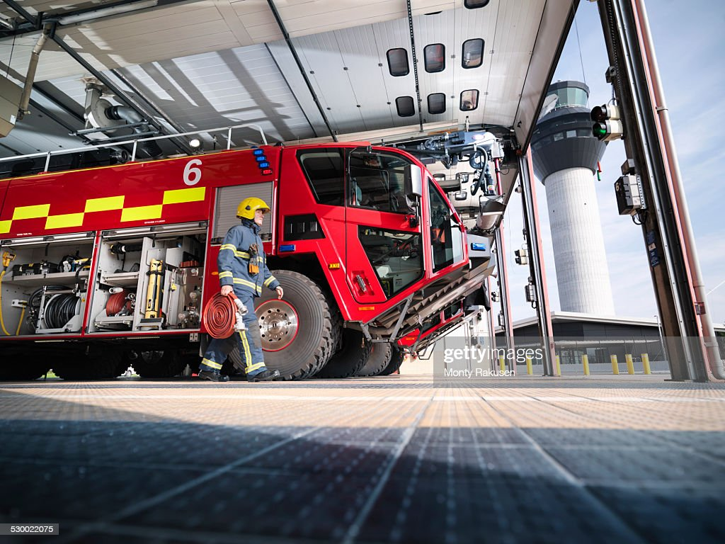 Fireman carrying equipment to fire engine in airport fire station : Stock Photo