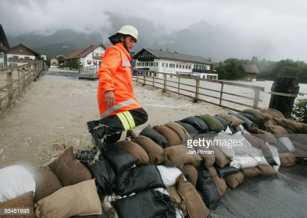 A fireman climbs over a barrier of sandbags on August 23 2005 in Eschenlohe Germany Heavy rainfall and floods in both Austria and Switzerland caused...