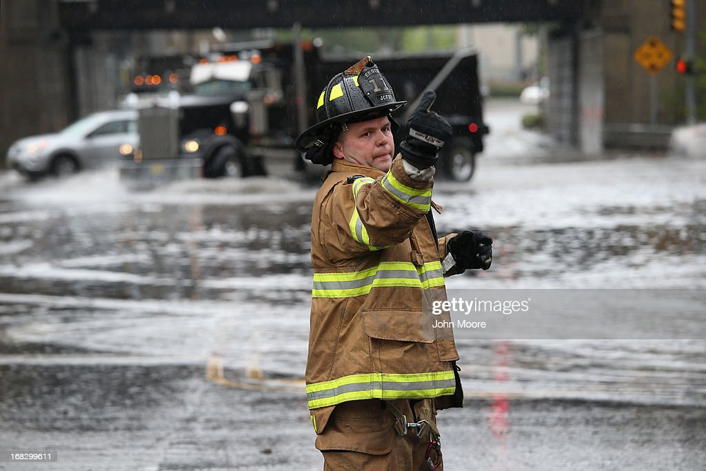 A fireman directs traffic away from a flooded underpass on May 8, 2013 in Jersey City, New Jersey. Heavy rains flooded streets, stranding some motorists during morning rush hour traffic.