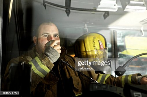 Fireman driving a truck while speaking on the radio : Stock Photo