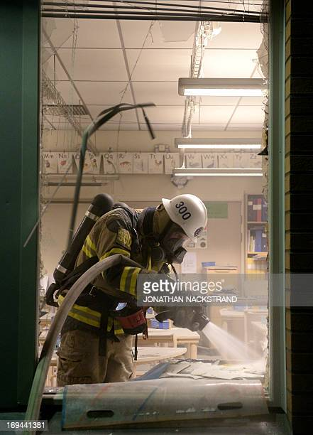 A fireman extinguish a burning school room in the Stockholm suburb of Tensta after youths rioted in few different suburbs around Stockholm and Sweden...