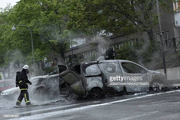 A fireman extinguishes a burning car in the Stockholm suburb of Rinkeby after youths rioted in several different suburbs around Stockholm Sweden for...