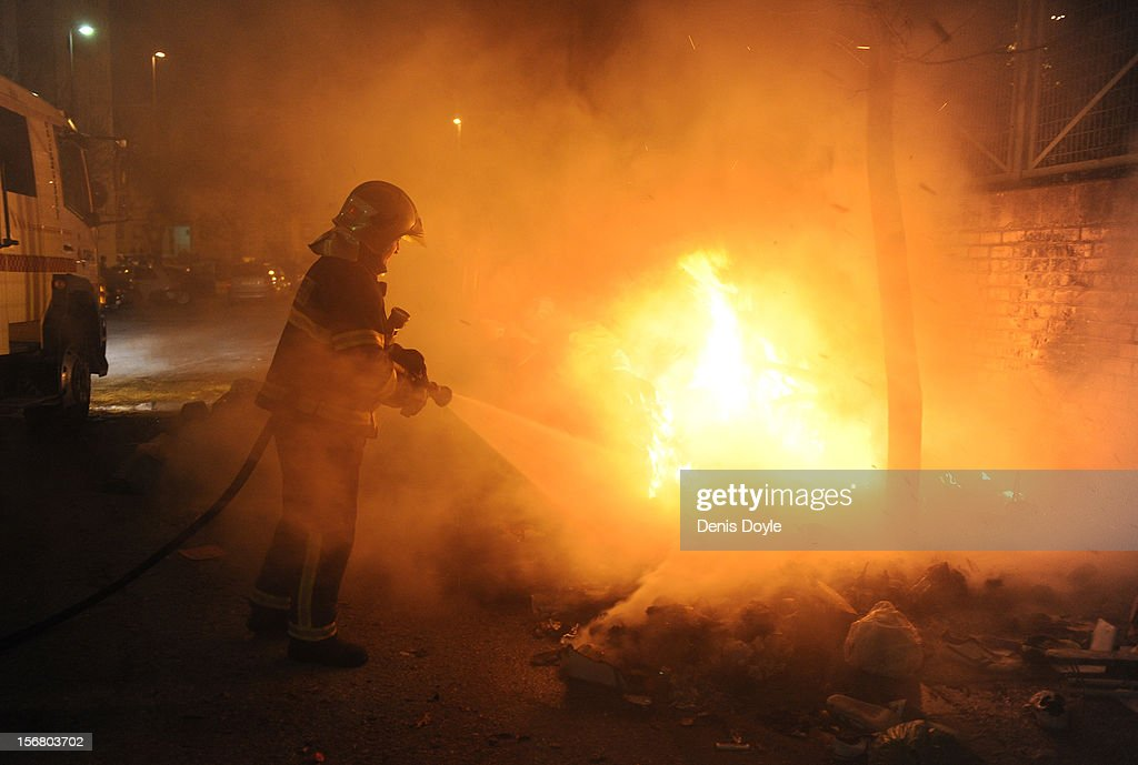 A fireman extinguishes a fire of burning garbage set by residents during the 20th day of the garbage collectors strike on November 21, 2012 in Jerez de la Frontera, Spain. Residents have begun burning the garbage during the strike by the collectors who are protesting planned layoffs in the sector by the local town council.