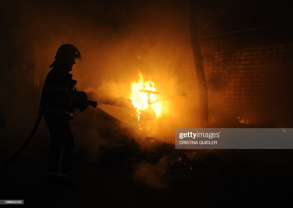 A fireman extinguishes a pile of uncollected rubbish set on fire by neighbors in a street of Jerez de la Frontera on November 21, 2012. Rubbish collectors have been on strike in the municipality of Jerez de la Frontera since November 5, 2012 to protest against the austerity cuts imposed by the town hall.