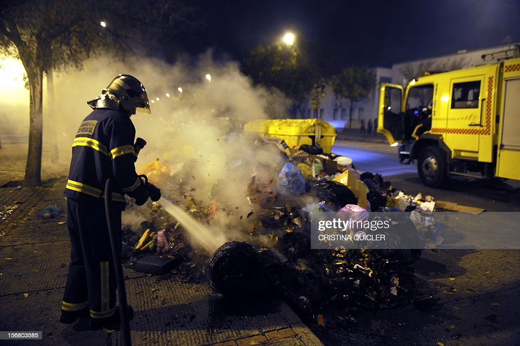 A fireman extinguishes a pile of uncollected rubbish set on fire by neighbors in a street of Jerez de la Frontera on November 21, 2012. Rubbish collectors have been on strike in the municipality of Jerez de la Frontera since November 5, 2012 to protest against the austerity cuts imposed by the town hall. AFP PHOTO/ CRISTINA QUICLER
