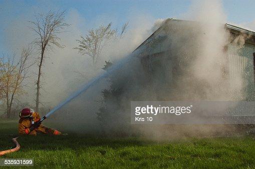 Fireman Fighting House Fire : Stock Photo