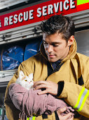 Fireman holding rescued cat, close-up