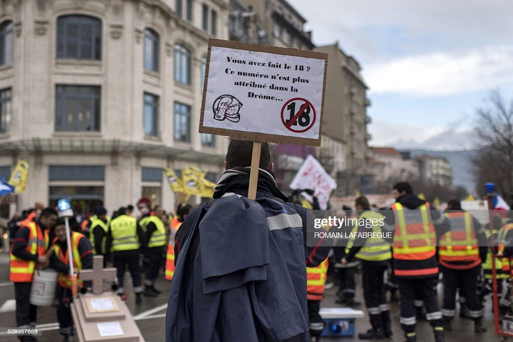 A fireman holds a placard reading 'You dialed the 18, this number is no longer assigned in the Drome department' marches in Valence central eastern France, along with firefighters from the Drome and 40 other French departments to protest against the closure of 19 emergency services and fire centers, on February 13, 2016. / AFP / ROMAIN LAFABREGUE