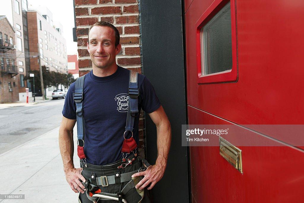 Fireman in front of firehouse on street, portrait