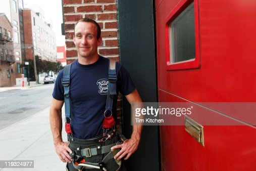Fireman in front of firehouse on street, portrait