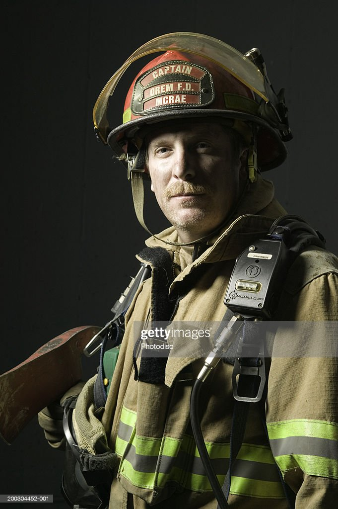 Fireman in full uniform holding axe in studio, portrait : Stock Photo
