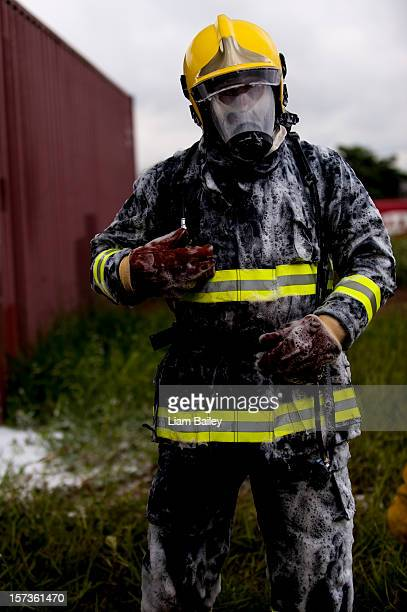 A fireman in protective clothing covered in foam