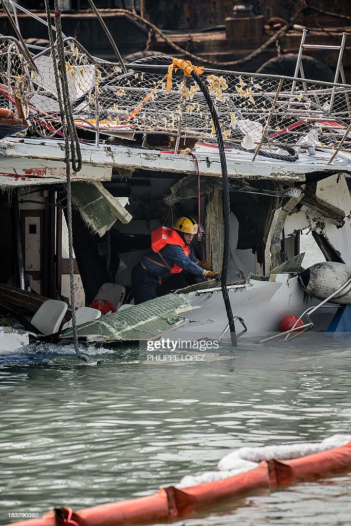 A fireman inspects the back end of the badly damaged Lamma IV passenger boat after a collision near the shores of Hong Kong's Lamma island on October...