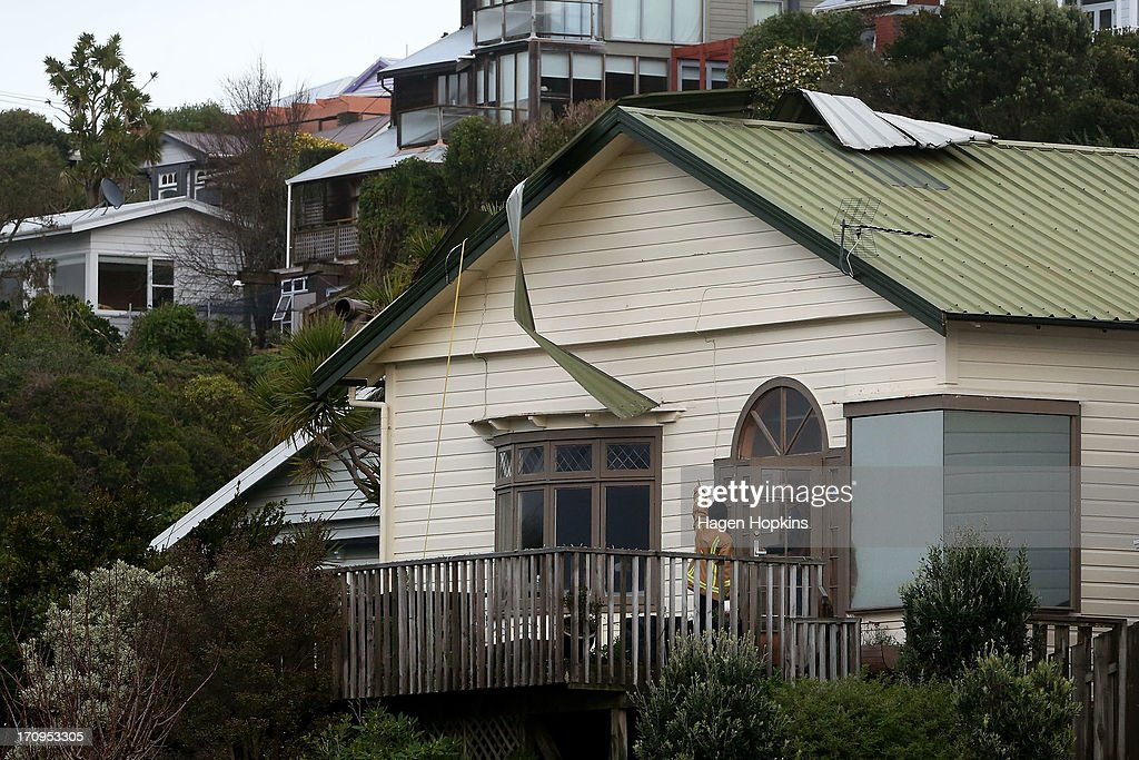 A fireman inspects the roof of a house in Brooklyn after being damaged by a large storm on June 21, 2013 in Wellington, New Zealand. Winds reached up to 200km per hour during the storm and around 30,000 homes were left without power across the Wellington region.
