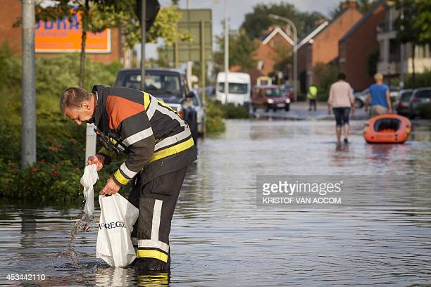 A fireman is at work in a flooded street with an inflatable boat after a rain storm in Merksplas on August 10 2014 AFP PHOTO/BELGA PHOTO KRISTOF VAN...