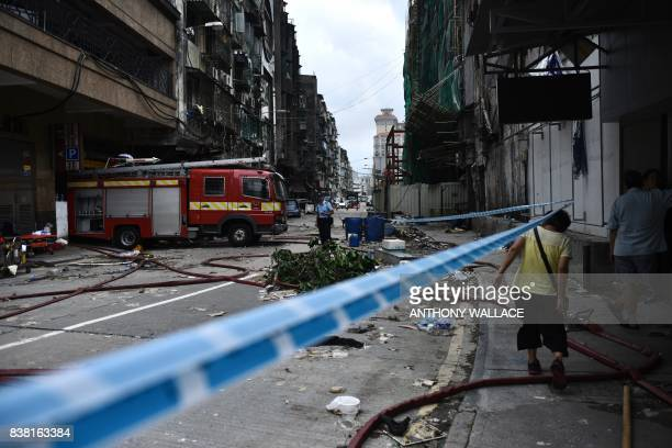 A fireman is seen next to a fire truck in a cordoned off residential area in Macau on August 24 a day after Typhoon Hato hit the city The death toll...