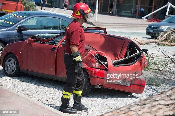 A fireman looks at the damage caused by last night tornado on a parked car on July 9 2015 in Venice Italy A tornado swept through the outskirts of...