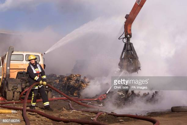 A fireman one of more than 110 who were tackling a blaze in Jordan's Scrap Yard at North Quay Newhaven East Sussex where at least 2000 scrap cars...