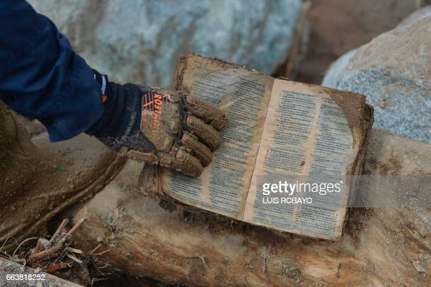 A fireman picks up a Bible from the rubble left by mudslides following heavy rains in Mocoa Putumayo department southern Colombia on April 2 2017 The...