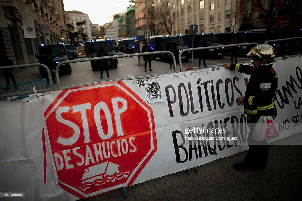 A fireman places a banner reading 'Stop evictions. Politicians and bankers' near the Parliament at Neptuno Square during a march by thousands of people on February 23, 2013 in Madrid, Spain. Public health workers, civil servants and disaffected citizens converged on central Madrid to protest against the austerity measures of Prime Minister Mariano Rajoy.