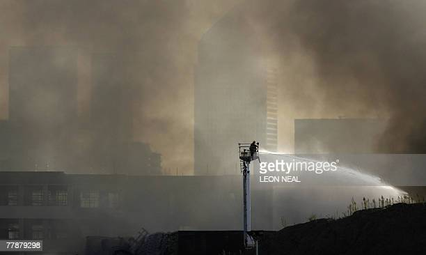 A fireman pours water onto the smouldering remains of a bus garage against the backdrop of Canary Wharf in east London 12 November 2007 A fire broke...