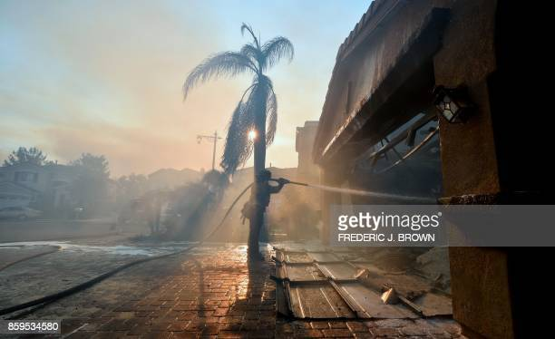 A fireman puts out a fire from homes in the Anaheim Hills neighborhood in Anaheim California on October 9 after a fire spread quickly through the...