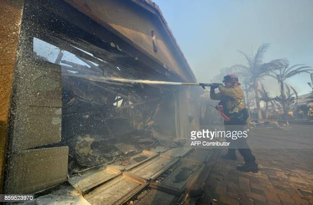 A fireman puts out a fire in a home at an Anaheim Hills neighborhood in Anaheim California on October 9 after a fire spread quickly through the area...