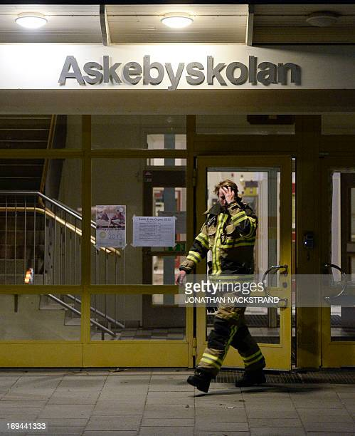 A fireman reacts after extinguishing a burning school room in the Stockholm suburb of Tensta after youths rioted in few different suburbs around...