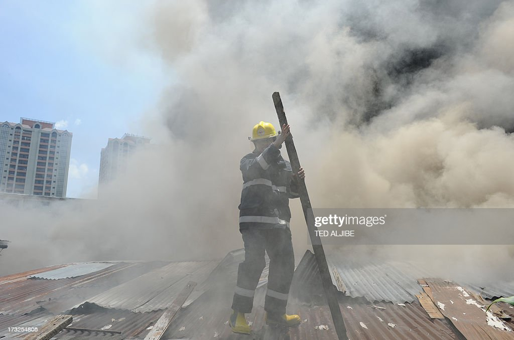 A fireman removes part of a roof as he to tries to extinguish burning houses as a fire engulfs a shanty town at the financial district of Manila on July 11, 2013, leaving more than 1,000 people homeless according to city officials. There were no immediate reports of casualties from the blaze, which occurred mid-morning amid government plans to relocate thousands of families living in areas vulnerable to floods and typhoons.