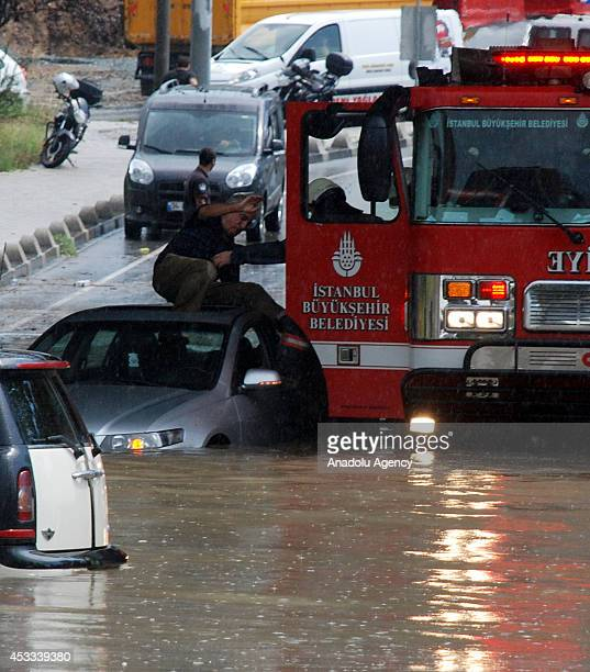 A fireman rescues a man who is stuck in his car due to flood waters after heavy rain in Anatolian side of Istanbul Turkey on 8 August 2014
