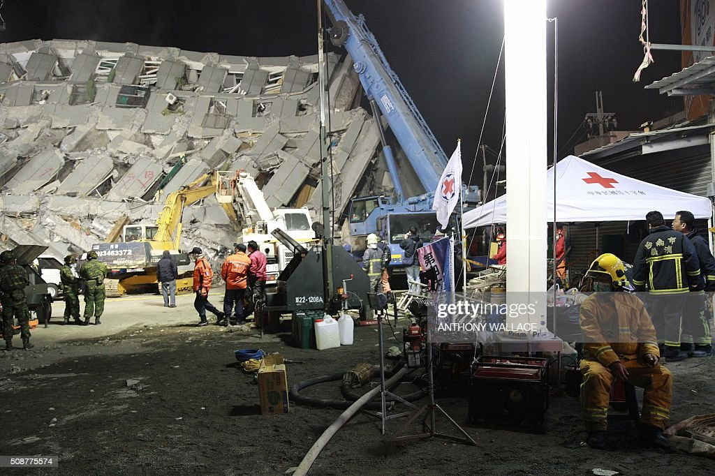 A fireman (R) rests during a rescue operation at the site of a collapsed building in the southern Taiwanese city of Tainan late on February 6, 2016 following a strong 6.4-magnitude earthquake. Relatives of residents trapped in a 16-storey apartment complex felled by a powerful earthquake in Taiwan that killed 14 people were praying for miracles Saturday as rescuers sought survivors, with more than 150 missing in the quake zone. / AFP / ANTHONY WALLACE