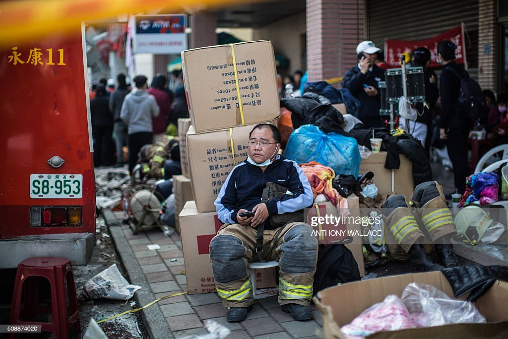 A fireman (C) rests near a collapsed building in the southern Taiwanese city of Tainan on February 7, 2016, following a strong 6.4-magnitude earthquake that struck early on February 6. Rescuers raced on February 7 to free more than 120 people buried under the rubble of an apartment complex felled by an earthquake in southern Taiwan that left 24 confirmed dead, as an investigation began into the collapse. AFP PHOTO / ANTHONY WALLACE / AFP / ANTHONY WALLACE