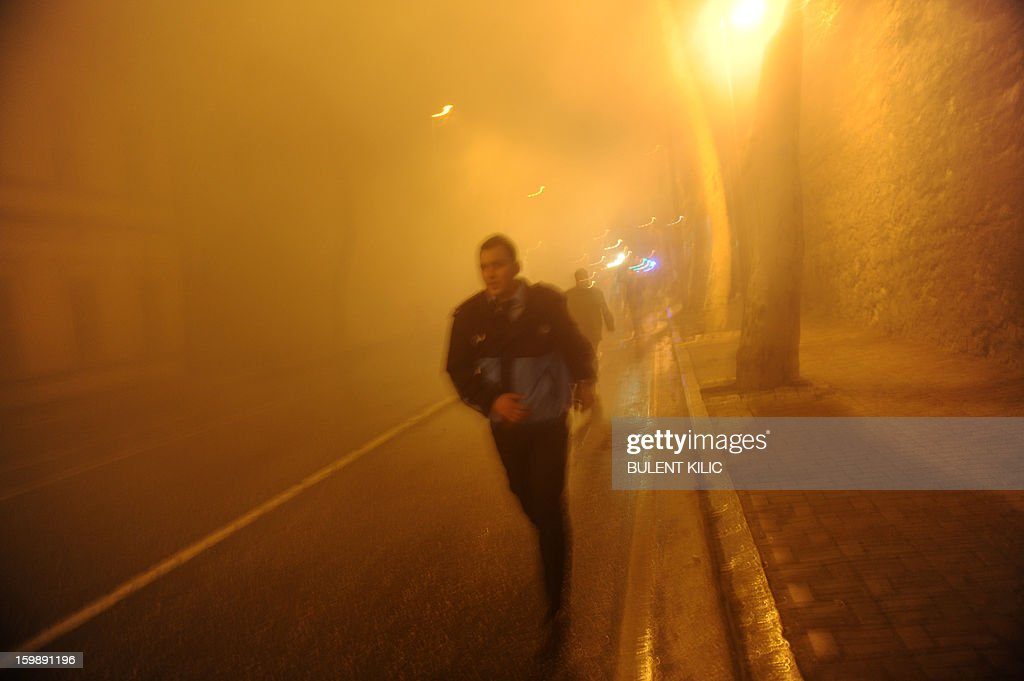 A fireman runs as Istanbul fireteams try to control flames during a fire at Galatasaray University on January 22, 2013, in Istanbul. AFP PHOTO/BULENT KILIC