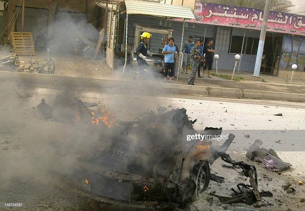 A fireman runs behind the burning carcass of a car following two car bombs explosions in the Iraqi city of Ramadi in the western Anbar province on April 19, 2012, as a wave of bombings and shootings across Iraq killed more than 35 people and wounded dozens more.