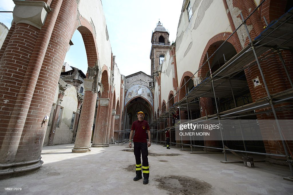 Fireman Salvatore Cardaci, coordinator of works, looks at the top of the damaged church (duomo) in Mirandola on May 22, 2013 a year after an earthquake in the Emilia Romagna. Reconstruction efforts in Emilia Romagna in Italy are proceeding slowly a year after two powerful earthquakes wrecked homes and businesses in this rich farming and medical industry region.