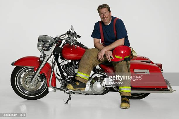 Fireman sitting on large red motorbike in studio, portrait