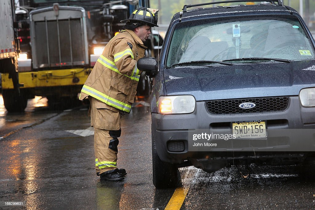 A fireman speaks with a motorist while directing traffic away from a flooded underpass on May 8, 2013 in Jersey City, New Jersey. Heavy rains flooded streets, stranding some motorists during morning rush hour traffic.