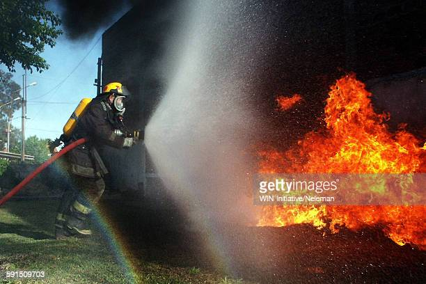 Fireman spraying fire from burning home