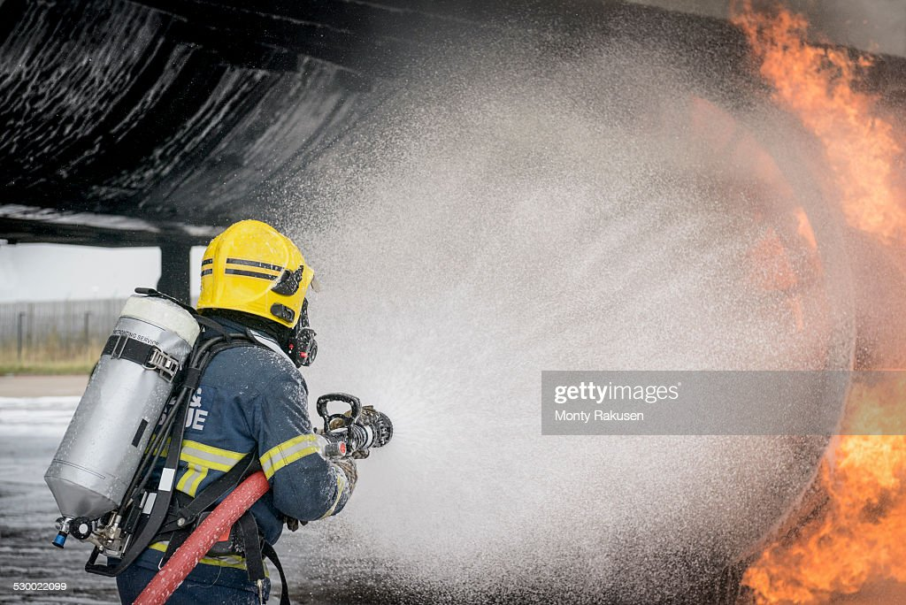 Fireman spraying water on simulated aircraft fire at training facility : Stock Photo